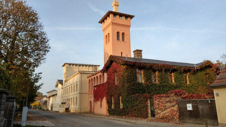 Gutshaus im italienischen Landhaus-Stil, rötlich mit Turm, teils mit Efeu bewachsen, daneben weitere helle historische Bauten