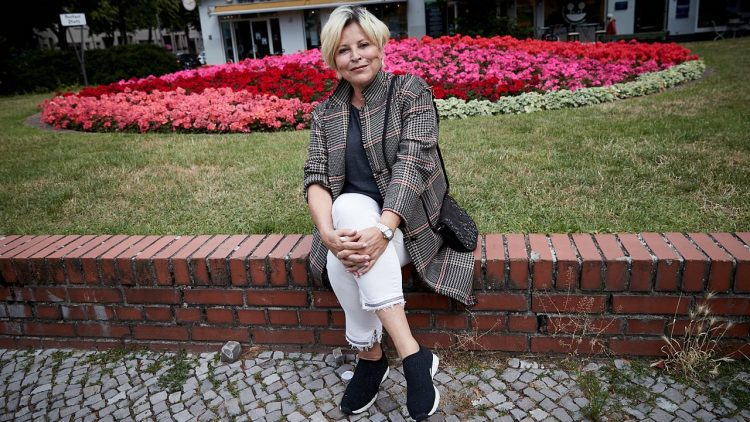 Elisabeth Herrmann, blonde Haare, karierte Jacke, weiße Hose, sitzt vor Rasen mit großem Blumenbeet, Häuser dahinter