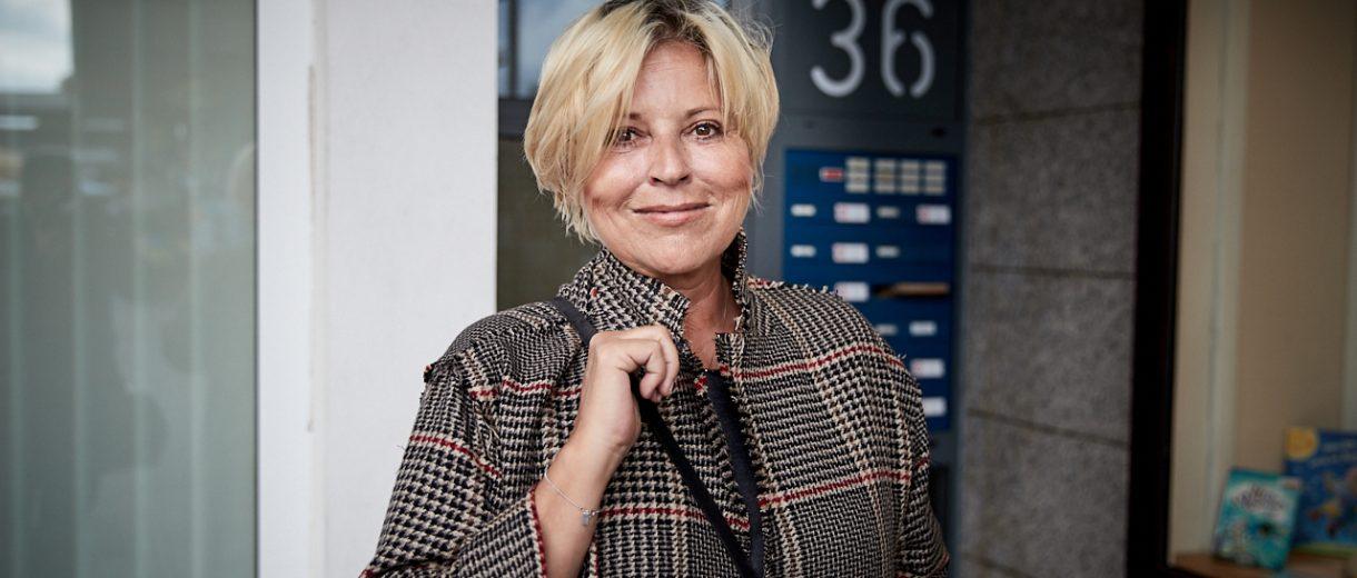 Elisabeth Herrmann, blonde Haare, karierte Jacke, Handtasche, steht vor Haus