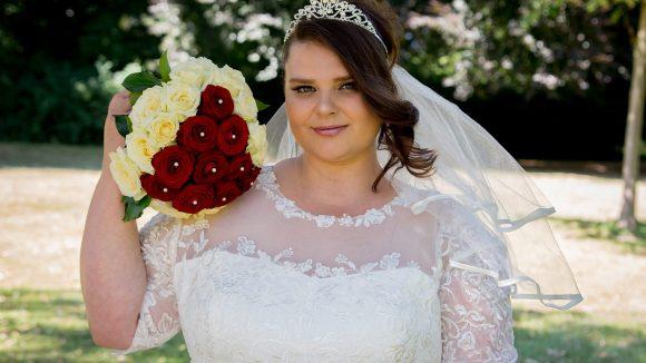 Braut mit einem Strauß aus roten Rosen