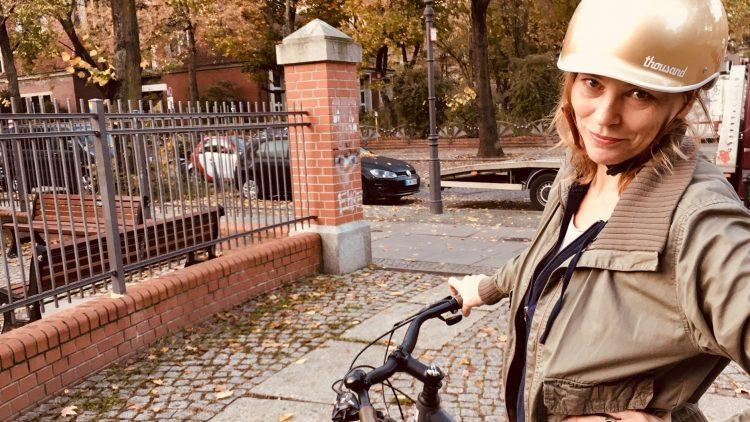 Frau mit goldenem Fahrradhelm und Fahrrad.