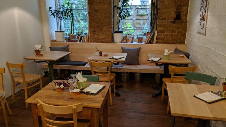 Inneneinrichtung mit Holzmöbeln, Pflanzen und Büchern.