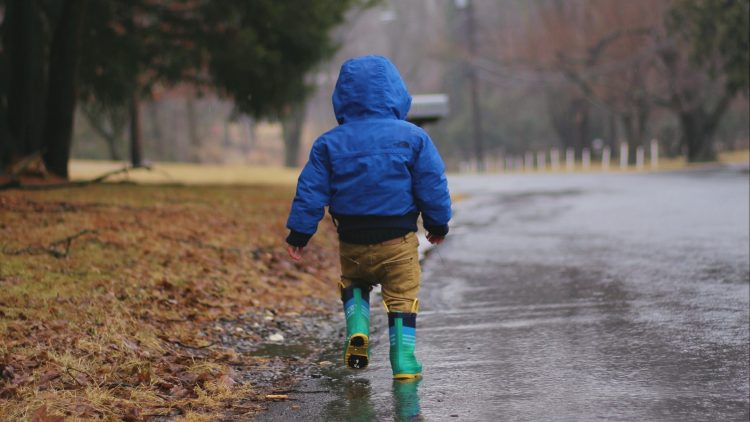 Kind von hinten mit blauer Jacke und Gummistiefeln im Regen