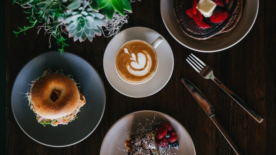 Aufnahme von Cafe Tisch mit Bagel, Cappuccino, Pancakes und Kuchen