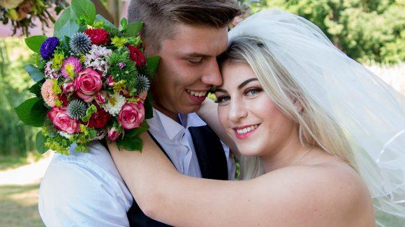 Brautpaar umarmt sich und sieht in die Kamera.
