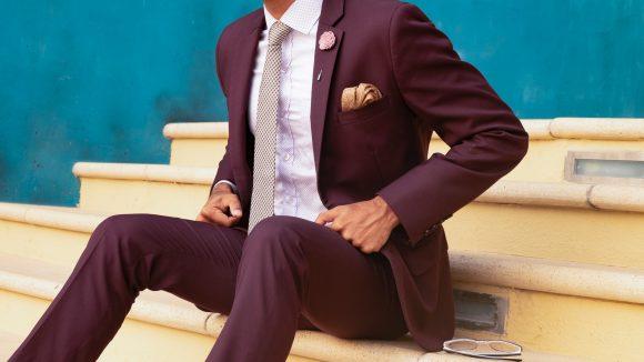Mann im bordeauxroten Anzug, mit Krawatte und Hemd, Kopf nicht zu sehen, sitzt auf Treppe