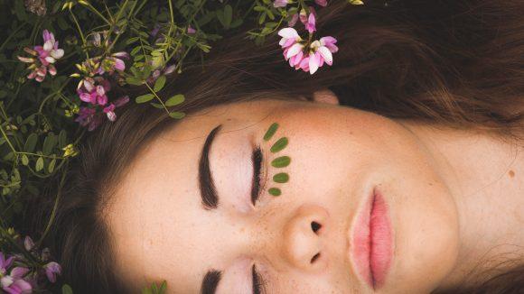Eine Frau liegt in mitten von Blumen, geschminkt und mit grünen Punkten unter dem linken Auge.