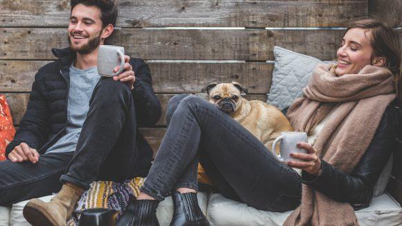 Ein Pärchen sitzt auf einer Holzbank mit einem kleinen Hund.