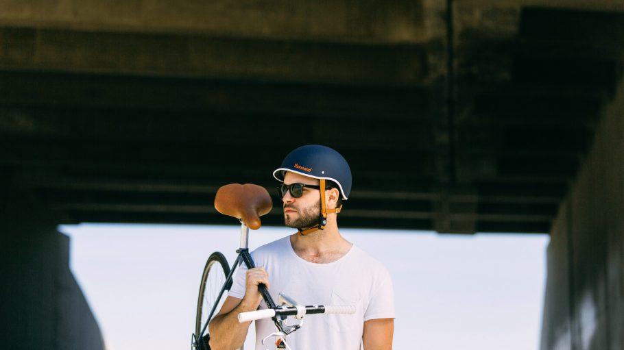 Ein Mann trägt sein Rennrad.