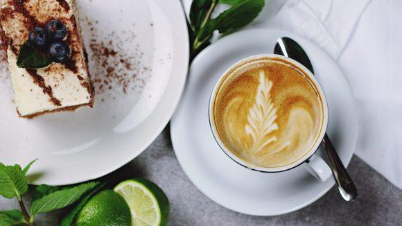 Eine Tasse Kaffee mit Muster oben und ein Teller mit rechteckigem Stück Kuchen, der mit drei Blaubeeren garniert ist