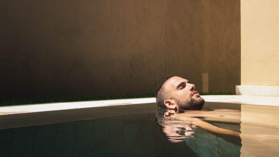 Mann entspannt mit geschlossenen Augen im Pool