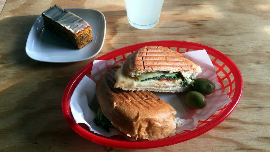 Sandwich in Plastikschale, im Hintergrund Limo und Stück Kuchen.