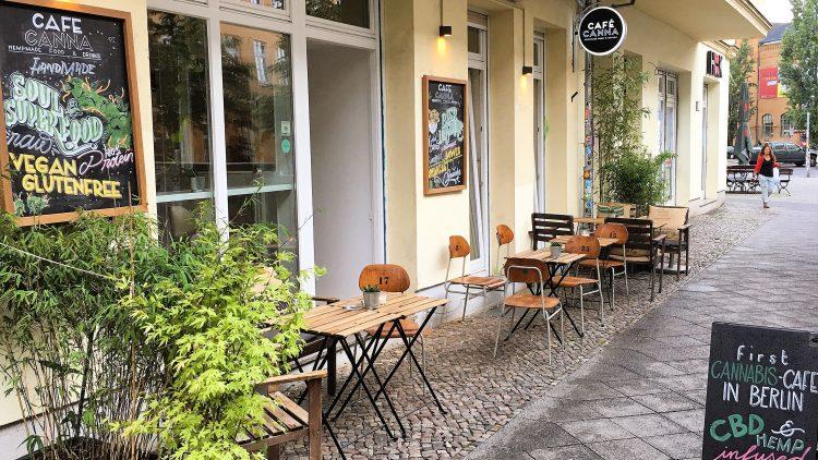 CBD-Café in Berlin mit Hanfpflanze und Holzstühlen vor der Tür