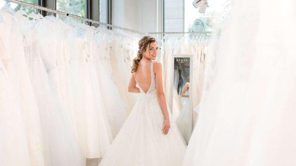 Frau in Breitkleid zwischen weiteren Brautkleidern