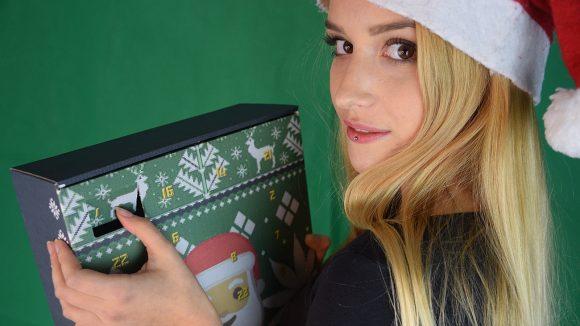 Frau mit langen blonden Haaren und Weihnachtsmütze hält Adventskalender