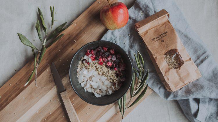 Hanfsamen Müsli mit Beeren und Kokos in einer Schale auf einem Holzkbrett. Dekoriert mit Zweigen, Apfel und einem Messer.