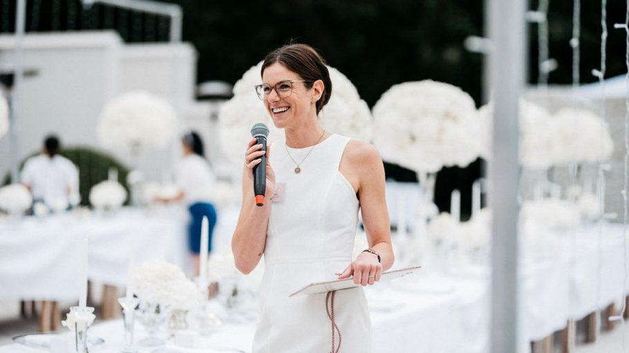 Frau in weißem Kleid mit Brille steht auf Bühne im Freien, im Hintergrund Hochzeitsgäste