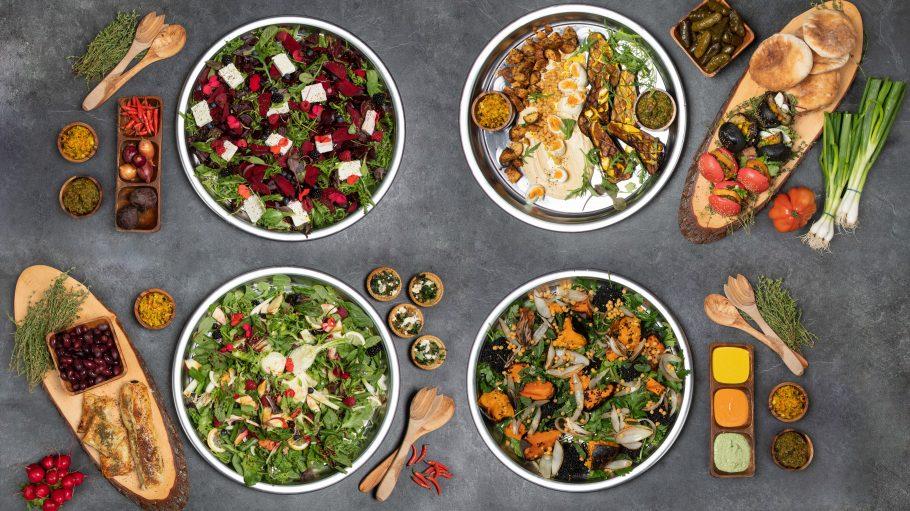 Schüsseln mit Salaten und Hummus
