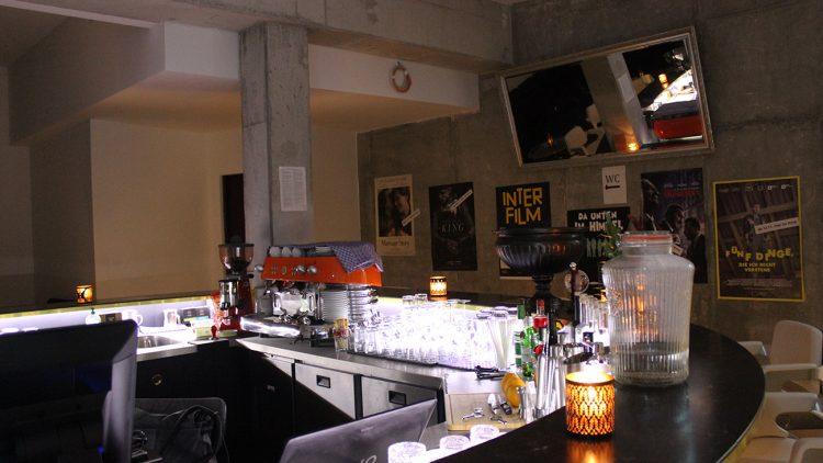 Bar mit Gläsern und Kaffeemaschine, an der Wand Spiegel und Filmplakate