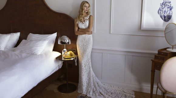 Frau in Brautkleid neben einem Bett