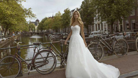 Frau in weißem Brautkleid auf einer Brücke