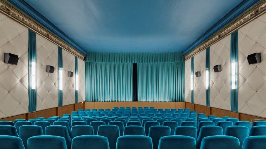 Kinosaal vom Neues Off in Berlin mit blauen Sesseln und Vorhang sowie beigem Samt an der Wand