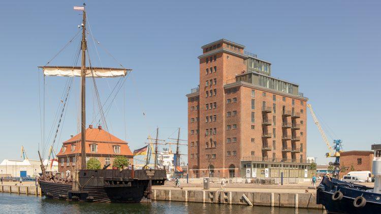 Speichergebäude neben Hafenbecken mit Segelschiff