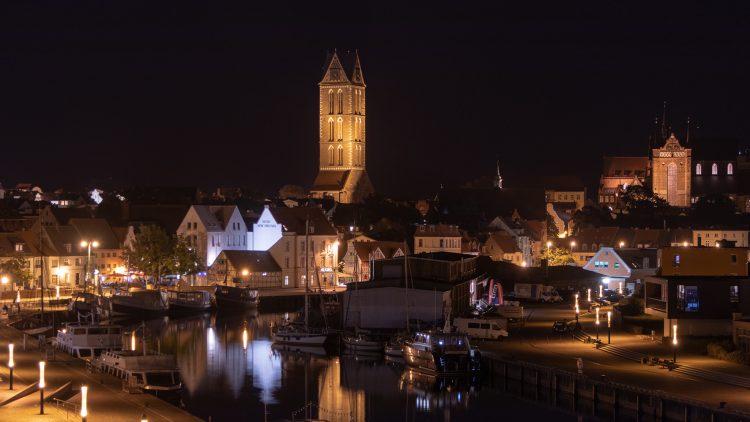 Altstadt von Wismar bei Nacht, zwei Kirchen, Hafenbecken mit Booten