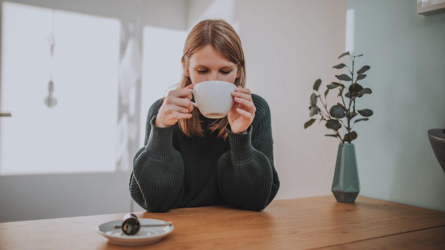 Frau trinkt Tee mit CBD vor Holztisch