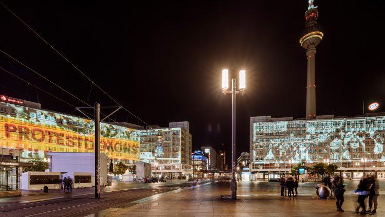 Alexanderplatz bei Nacht mit Fernsehturm und Videoprojektion auf Gebäuden