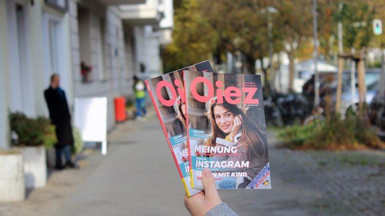 Hand hält zwei DIN A5-Hefte von QIEZ, dahinter Gehweg und Fassade