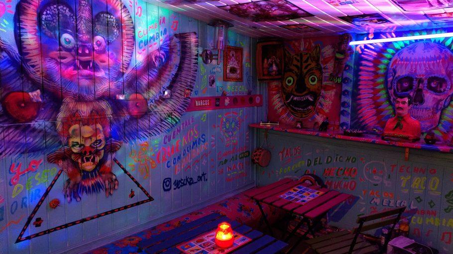 Bunt bemalter Innenraum eines Containers mit mexikanischen Tiergestalten und Totenkopf, Klapptische und Stühle