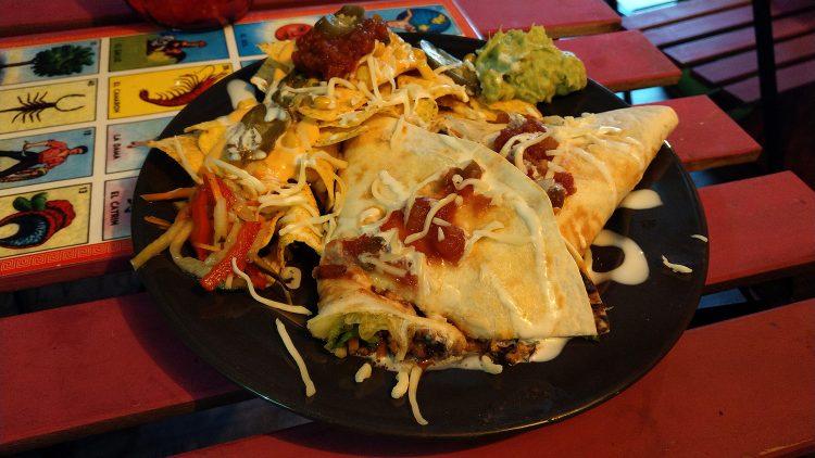 Teller mit mexikanischem Essen: Tortillas mit Füllung, Pasten, Nachos mit Käsesoße