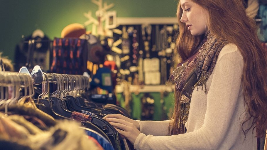 Eine blonde Frau steht vor einem Kleiderständer und shoppt.