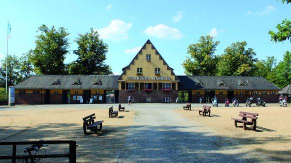Eingang des Strandbads Wannsee: Gelbes Haus mit Aufschrift, links und rechts die Eingänge