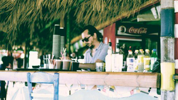 Barkeeper an Beach Bar mit Dach aus Palmenwedeln mixt Drink