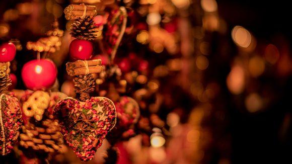 Weihnachtsmarkt Stand mit Deko-Artikeln, gebastelten Herzen, Äpfeln und Tannenzapfen