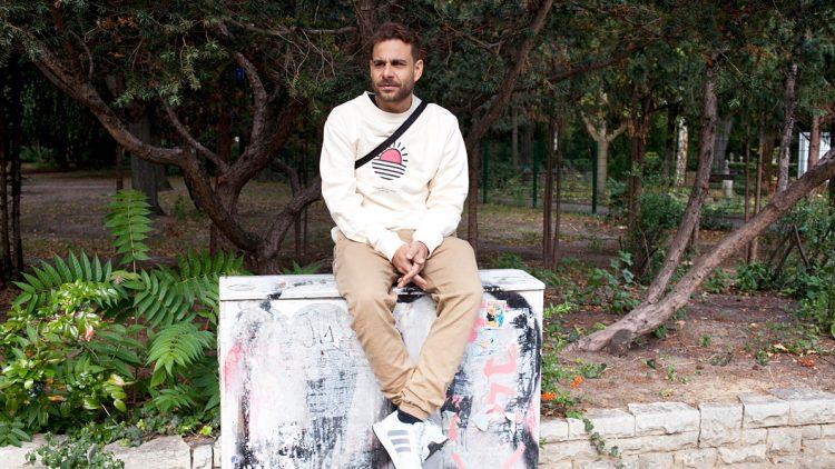 Rapper Mädness sitzt auf Stromkasten