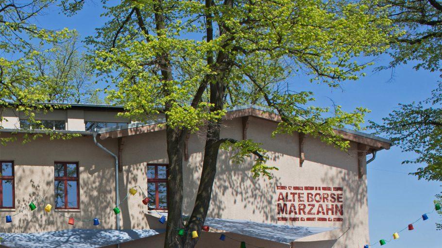 Weißes Haus mit Aufschrift Alte Börse Marzahn, davor Baum, blauer Himmel
