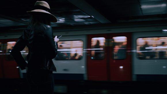 Frau mit Hut vor Zug