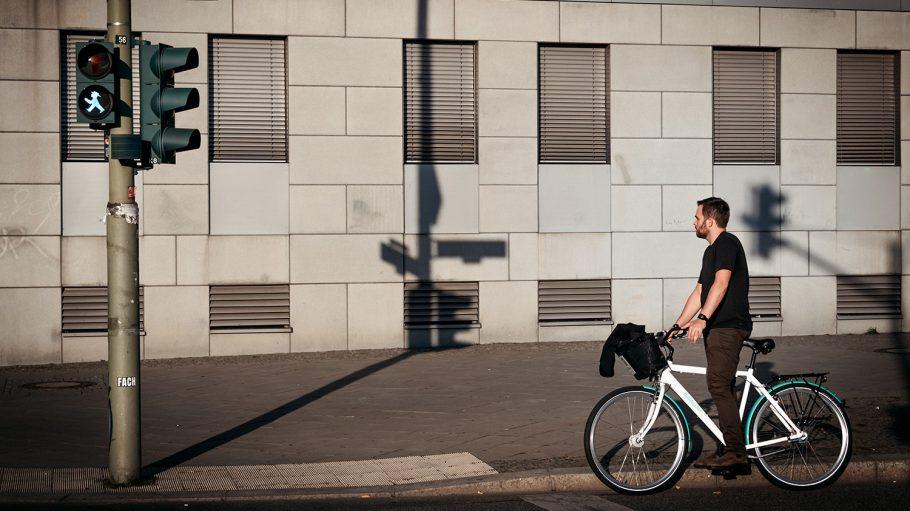 Radfahrer in schwarzem T-Shirt wartet in Berlin auf weißem Rad an Ampel, Straßenschild Mühlenstraße
