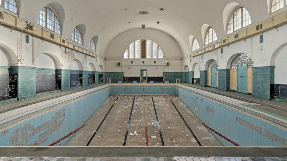Leere Schwimmhalle in Bogenform, Bogenfenster, Wandbögen, leeres Becken