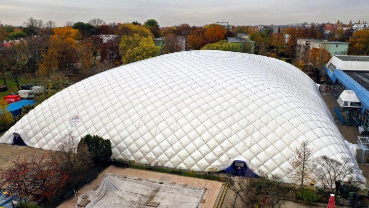 Traglufthalle, die wie großes weißes Kissen aussieht, steht vor Bäumen und Mietshäusern