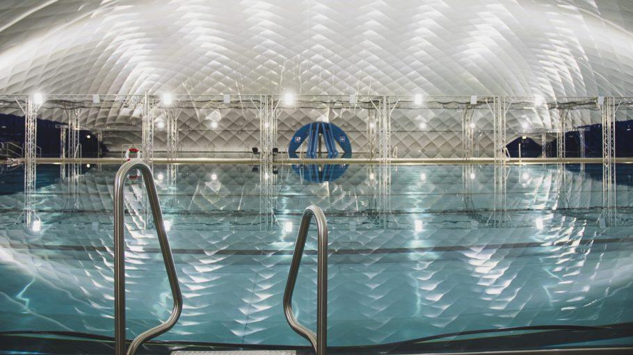 Schwimmbad mit weißem Tragluftdach, Lichter werden im Wasser reflektiert