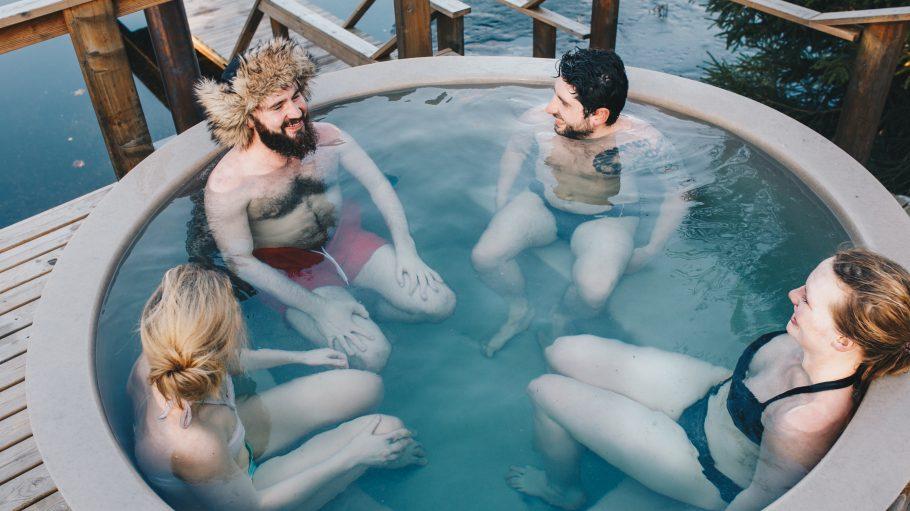 Vier Menschen sitzen im Whirlpool outdoor am See