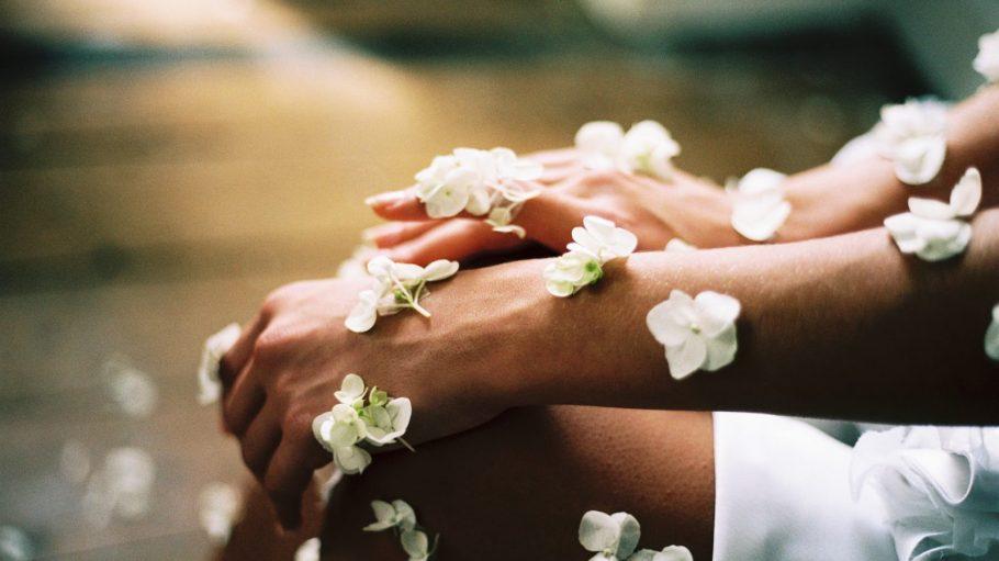Frauenhände und Knie mit weißen Blüten bedeckt