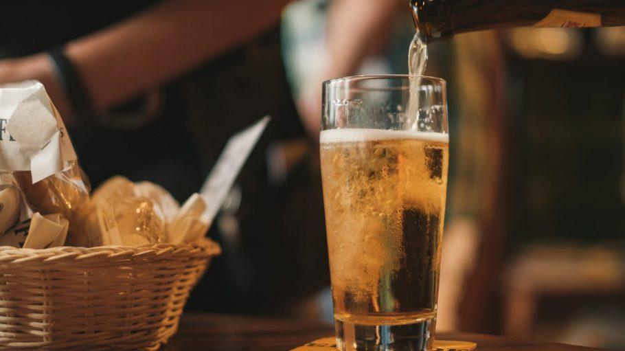 Bierglas, in das eine Hand Bier eingießt.