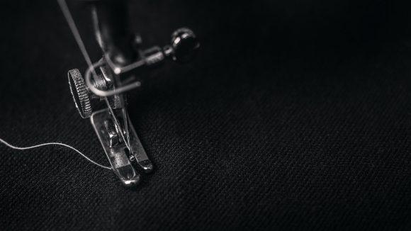 Nähmaschinenfuß auf schwarzem Stoff