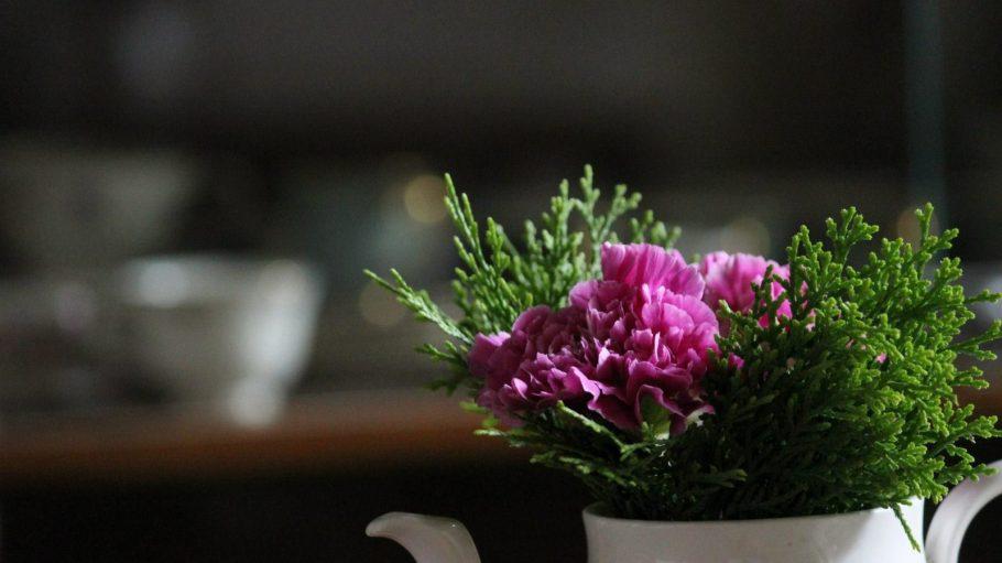 Ein pinker Blumenstrauß in einer Teetasse.