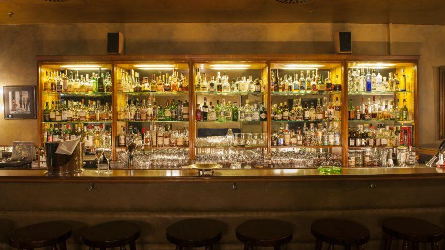Bar mit vielen Flaschen im Hintergrund und Stühlen vorne